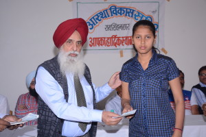 Dr. Gurmeet Singh, MD, President of Astha Vikas Samiti in Rajasthan, an NGO supported by IFCARE is handing over a chcke to Kum. Anjali Sain, a student in the local school.